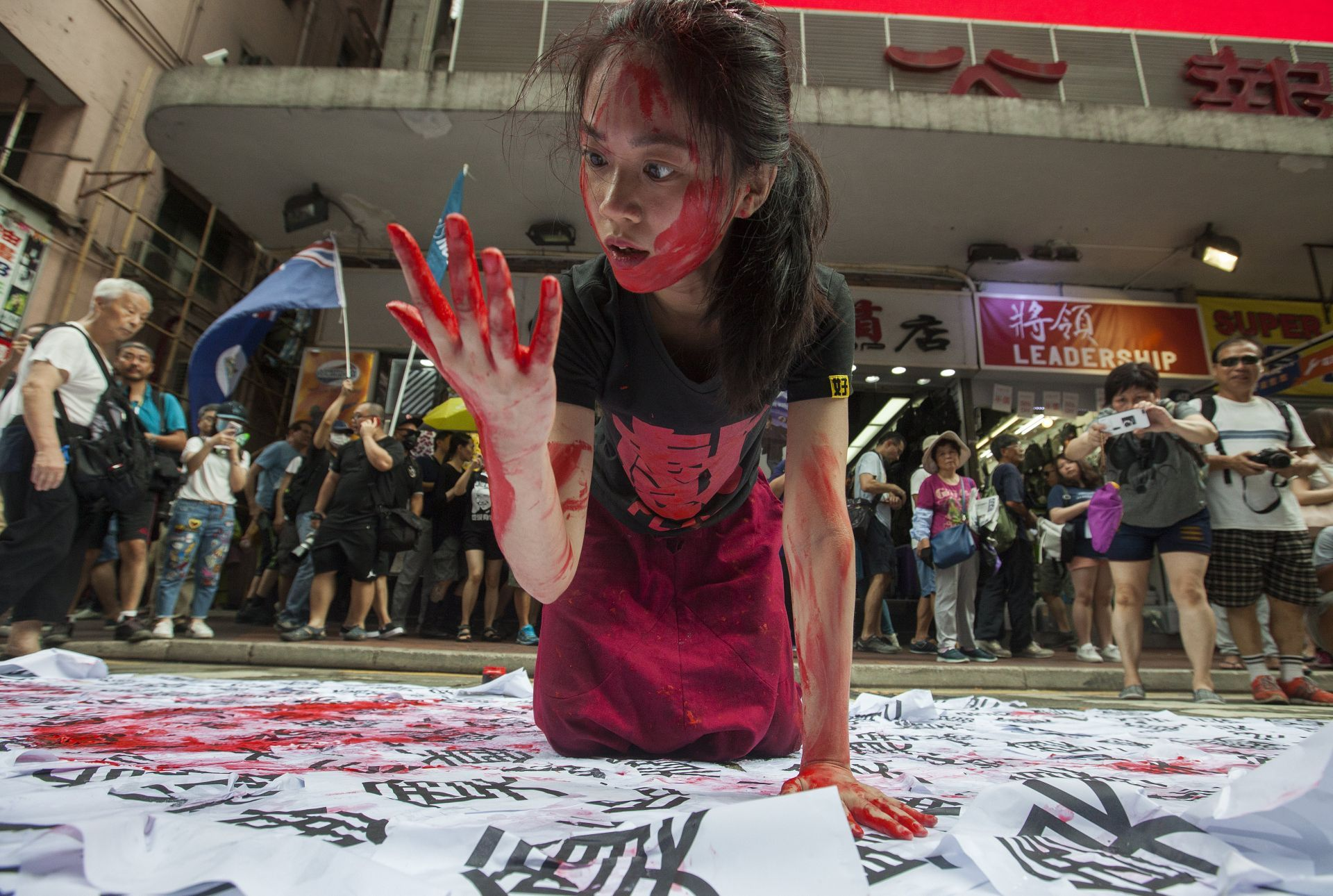 A pro-democracy performance artist acts on the theme of Chinese totalitarian rule in the streets of Hong Kong