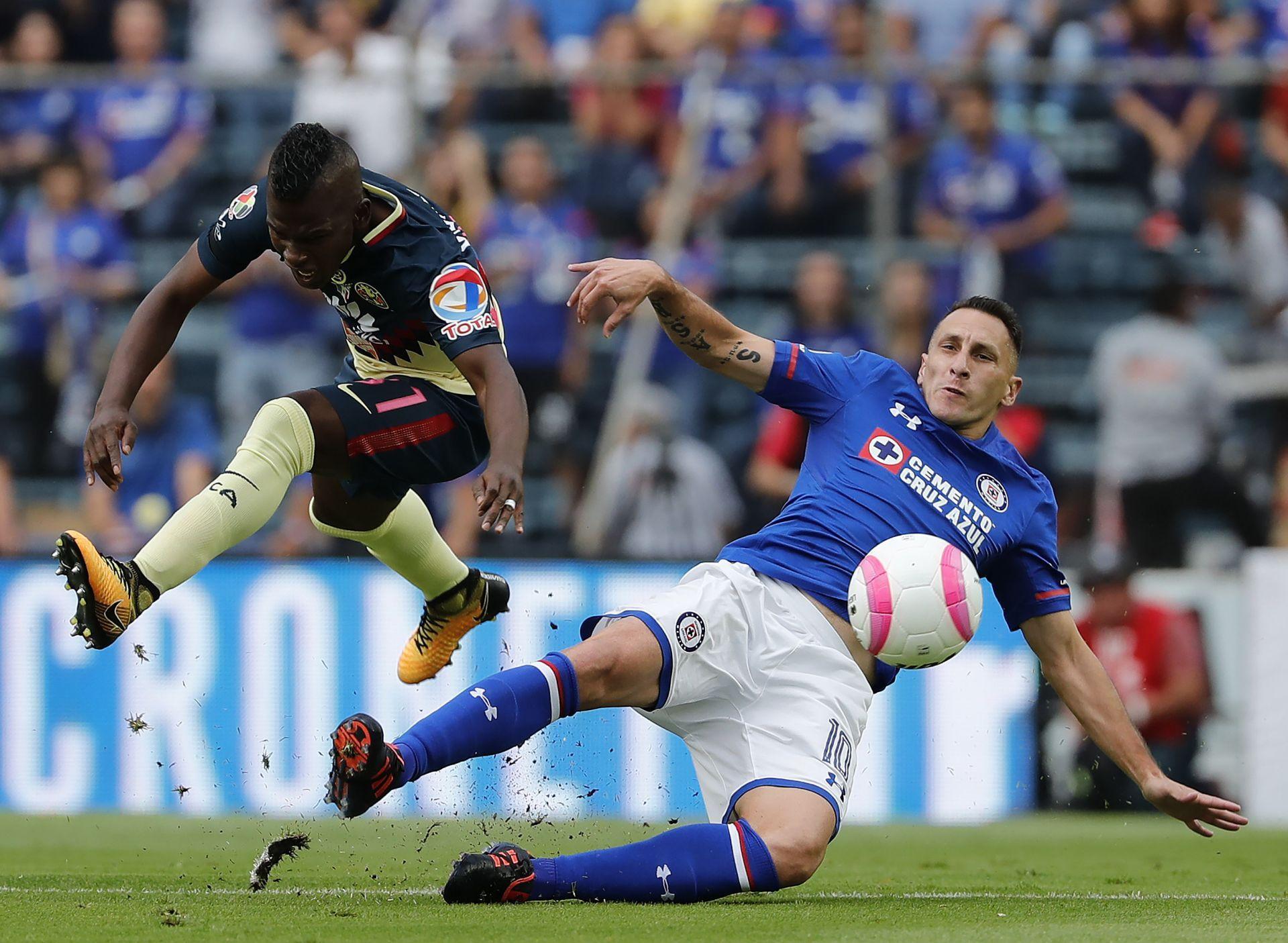El jugador de Cruz Azul Christian Giménez (d) disputa el balón con Carlos Quintero (i) del América, sábado 14 de octubre de 2017, durante un partido correspondiente a la jornada 13 de la liga mexicana de fútbol disputado en el estadio Azul de la Ciudad de México (México).