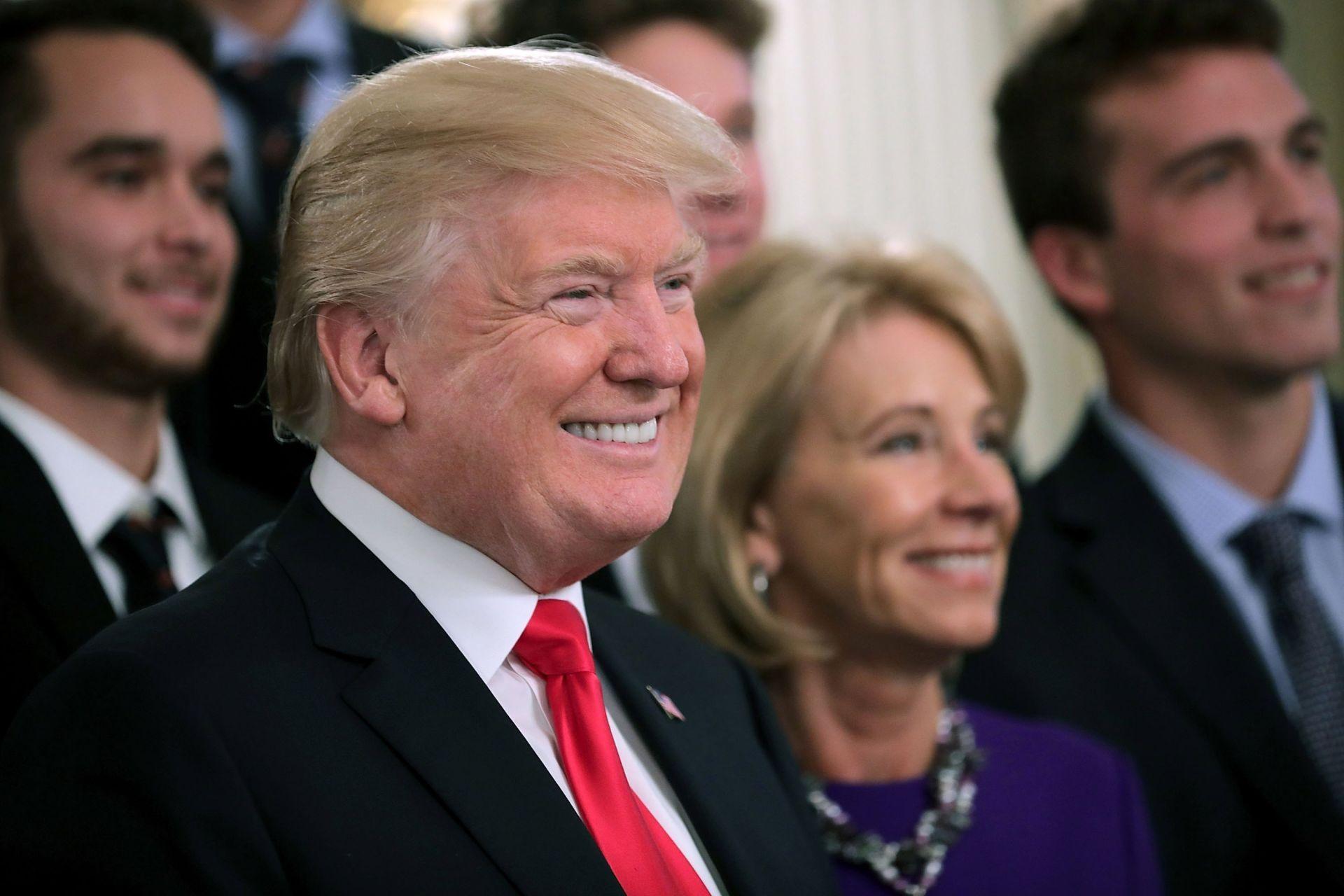 El presidente de los Estados Unidos, Donald J. Trump, y la secretaria de Educación, Betsy Devos, posan junto al equipo masculino de tenis la Universidad de Virginia.