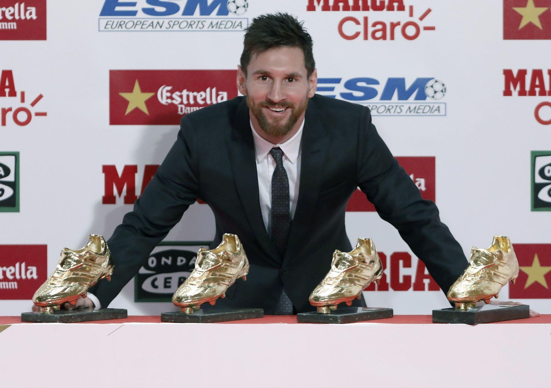 El delantero argentino del FC Barcelona, Lionel Messi, posa para la prensa gráfica, tras recibir la Bota de Oro por la temporada 2016-2017, con los cuatro galardones que ha recibido en su carrera en la gala que se ha celebrado hoy en Barcelona.