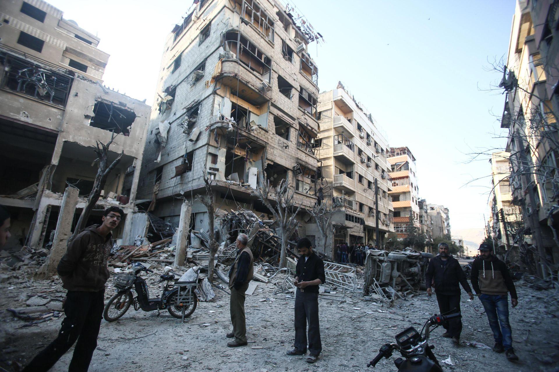 Gente inspecciona edificios después del ataque aéreo en Douma, Siria.