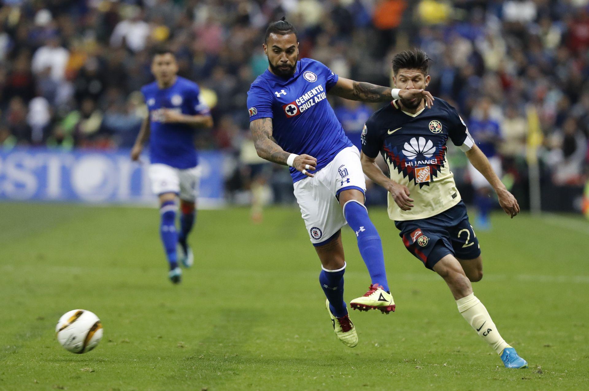 El jugador de América Oribe Peralta (d), disputa el balón con Julián Velázquez (i), de Cruz Azul
