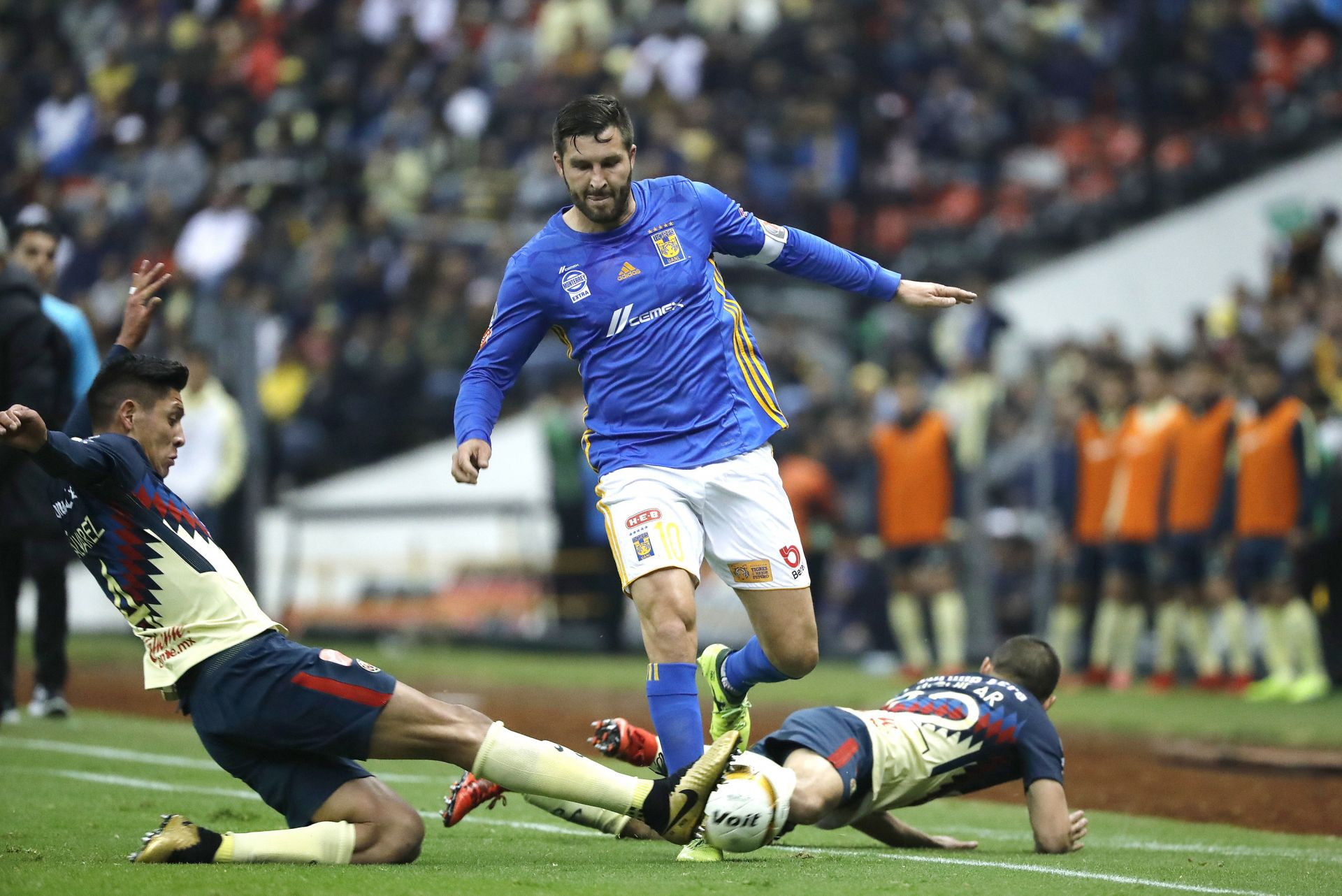Los jugadores del América Edson Álvarez (i) y Paul Aguilar (d) disputan el balón con André-pierre Gignac (c) de Tigres.
